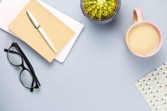 Bureau plat de siège social de configuration Espace de travail femelle avec le carnet, lunettes, tasse de thé, journal intime, us Image libre de droits