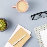 Bureau plat de siège social de configuration Espace de travail femelle avec le planificateur, lunettes, tasse de thé, journal int Photographie stock libre de droits
