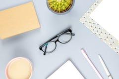 Bureau plat de siège social de configuration Espace de travail femelle avec le planificateur, lunettes, tasse de thé, journal int Photo libre de droits