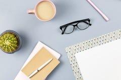 Bureau plat de siège social de configuration Espace de travail femelle avec le planificateur, lunettes, tasse de thé, journal int Images libres de droits