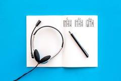 Bureau van musicus voor songwriter het werk met hoofdtelefoons en nota's blauwe hoogste mening als achtergrond royalty-vrije stock foto