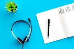 Bureau van musicus voor songwriter het werk met hoofdtelefoons en nota's blauwe hoogste mening als achtergrond stock foto