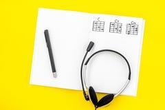 Bureau van musicus voor songwriter het werk met hoofdtelefoons en nota's gele hoogste mening als achtergrond stock fotografie