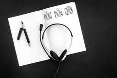 Bureau van musicus voor songwriter het werk met hoofdtelefoons en nota's zwarte hoogste mening als achtergrond stock fotografie