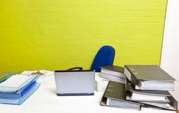 Bureau vide avec l'ordinateur portable, les dossiers et la chaise vide Image stock