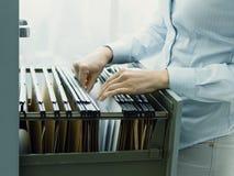 Bureaubediende die dossiers zoeken in de archiefkast stock afbeeldingen