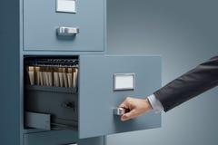 Bureaubediende die dossiers zoeken in een archiefkast royalty-vrije stock afbeeldingen