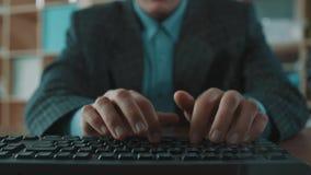 Bureaubediende in het blauwe overhemd van het plaidjasje snel snel op computertoetsenbord stock footage