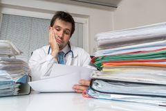 Bureaucracy in medicine concept. Tired overworked doctor is reading medical report. Many documents on desk.  Royalty Free Stock Photos