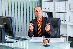 Bureaucratie bedrijfsmens die bij zijn bureau zegels bekijken stock afbeeldingen