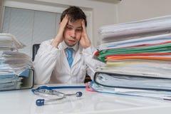 Bureaucratie in geneeskundeconcept De vermoeide overwerkte arts heeft vele documenten op bureau stock afbeelding