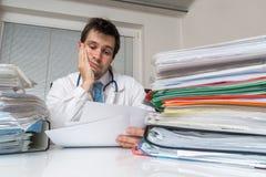 Bureaucratie in geneeskundeconcept De vermoeide overwerkte arts leest medisch rapport Vele documenten op bureau royalty-vrije stock foto's