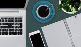 Bureaudesktop met diverse voorwerpen Laptop, kop van koffie of thee, smartphone en leeg notitieboekje die op bureau leggen werkru Stock Fotografie