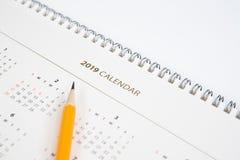 Bureaukalender en geel potlood op witte achtergrond stock afbeeldingen