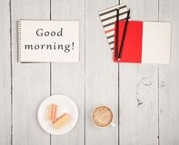 Bureaulijst met blocnotes en tekst & x22; Goedemorgen! & x22; , kop van koffie en wafels stock foto