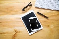 bureaulijst met computertoetsenbord, glazen, tabletpc en smar Stock Foto