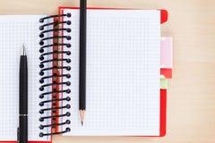 Bureaulijst met leeg blocnote, pen en potlood Stock Foto's