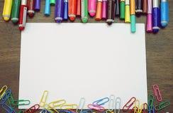 Bureaulijst met lege document pagina, kleurrijke pennen en paperclippen Hoogste mening met exemplaarruimte Royalty-vrije Stock Afbeeldingen