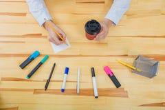 Bureaulijst met toebehoren: een wit blad van document, een blauw-roze teller, een glas koffie, een pen, een potlood en vrouwen stock afbeeldingen