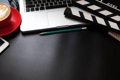 Bureaumateriaal met laptop van de Filmklep en de penblocnote van de koffiekop royalty-vrije stock foto's