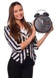Bureaumeisje die die klok tonen op een witte achtergrond wordt geïsoleerd stock foto's