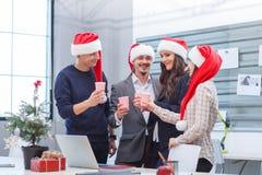 Bureauteam die pret hebben bij het Kerstmisbedrijf in het bureau stock afbeelding