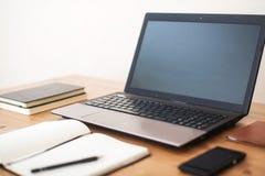 Bureauwerkplaats met laptop, slim telefoon en notitieboekje op houten lijst royalty-vrije stock afbeelding