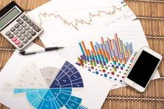 Bureauwerkplaats met PC, calculator en telefoon op grafieken of Stock Foto