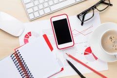 Bureauwerkplaats met telefoon, grafieken en koffie Stock Fotografie