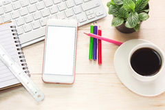 Bureauwerkruimte met de koffie van de toetsenbordblocnote van kop en smartphone op houten lijst Royalty-vrije Stock Afbeeldingen