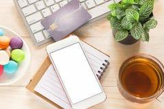 Bureauwerkruimte met de koffie van de toetsenbordblocnote van kop en smartphone op houten lijst Royalty-vrije Stock Foto's