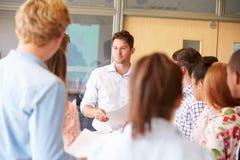 Bureaux se tenants prêt de With College Students de professeur dans la salle de classe Image stock