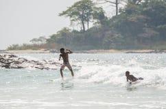 Bureh海滩,塞拉利昂- 2014年1月11日:冲浪在仅海浪斑点的两个未认出的年轻非洲男孩在国家 免版税库存图片