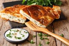 Burek turco relleno con espinaca y queso con crema agria sa imagenes de archivo