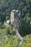 Burg Eltz. Castle Eltz in the forest near the Mosel river in Germany in sunlight with its turrets, entrance and road,and visitors taken from very high viewpoint Royalty Free Stock Photography