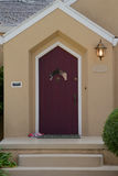 Burgandy door. Burgundy door with unusual window on a white trimmed beige house with a lamp Stock Image