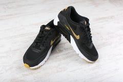 BURGAS BUŁGARIA, GRUDZIEŃ, - 29, 2016: Nike Wietrzy MAX kobiet ` s buty - sneakers w czerni, na białym drewnianym tle Obraz Royalty Free