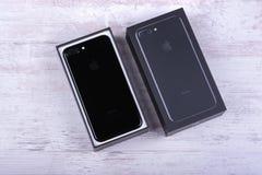 BURGAS, BULGÁRIA - 29 DE DEZEMBRO DE 2016: IPhone novo 7 Jet Black positiva de Apple, verso, no fundo de madeira branco Fotografia de Stock Royalty Free