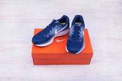 BURGAS, BULGARIA - SEPTEMBER 6, 2017: Nike Air Zoom Pegasus 34 Women`s Running Shoes in blue on white wooden background. Royalty Free Stock Images