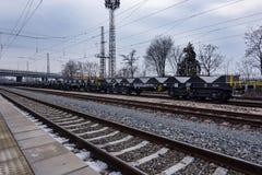 Burgas, Bulgarije - Januari 24, 2017 - de trein van de Vrachtlading - zwarte auto'swagens - Nieuwe axled vlakke wagen 6 - Type: S Stock Foto's