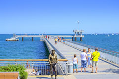 Burgas pier,Bulgaria. People walking on bridge pier and  sailing yachts race on hot summer day,Burgas city,Bulgaria Royalty Free Stock Image
