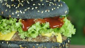 Burger ή χάμπουργκερ με ένα μαύρο κουλούρι και σπόροι σουσαμιού στο θολωμένο υπόβαθρο της κινηματογράφησης σε πρώτο πλάνο πρασίνω φιλμ μικρού μήκους