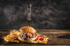 Burger βόειου κρέατος κινηματογραφήσεων σε πρώτο πλάνο κατ' οίκον γίνοντα με το μαχαίρι και τηγανητά στο ξύλινο TA στοκ εικόνες