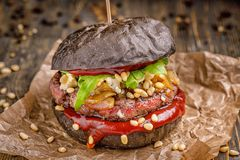 Burger βόειου κρέατος με ένα μαύρο κουλούρι, με το arugula και το τυρί και το κέτσαπ που ψεκάζονται με τα καρύδια πεύκων που εξυπ Στοκ Εικόνα