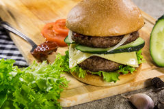 Burger βόειου κρέατος με το τυρί και τα λαχανικά στοκ εικόνα με δικαίωμα ελεύθερης χρήσης
