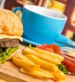 Burger και ο καφές αντιπροσωπεύουν έτοιμο να φάνε και να σπάσουν στοκ φωτογραφία