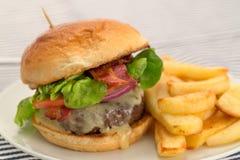 Burger και τηγανητά με ένα brioche κουλούρι Στοκ εικόνες με δικαίωμα ελεύθερης χρήσης