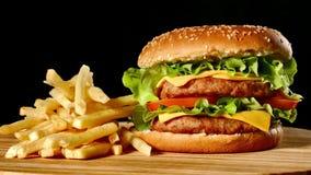 Burger και τηγανιτές πατάτες βόειου κρέατος τεχνών στον ξύλινο πίνακα που απομονώνεται στο μαύρο υπόβαθρο φιλμ μικρού μήκους