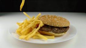 Burger και τηγανιτές πατάτες σε ένα άσπρο πιάτο απόθεμα βίντεο