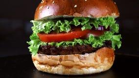 Burger κινηματογράφηση σε πρώτο πλάνο σε ένα μαύρο υπόβαθρο Πράσινα, ντομάτα, και κοτόπουλο ως συστατικά Burger r απόθεμα βίντεο